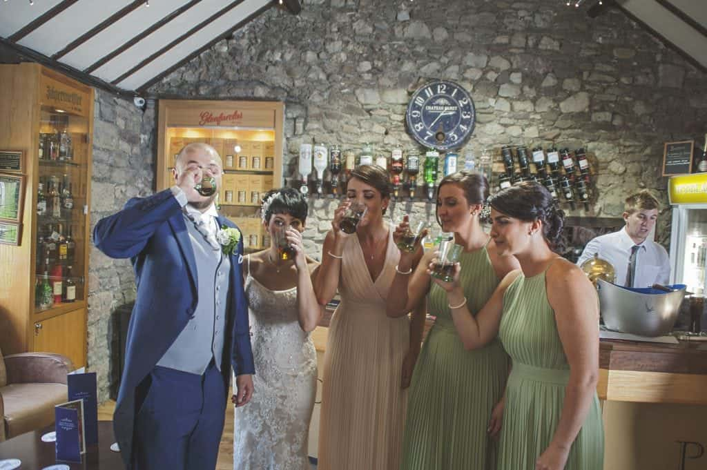 Groom, bride and bridesmaids doing shots