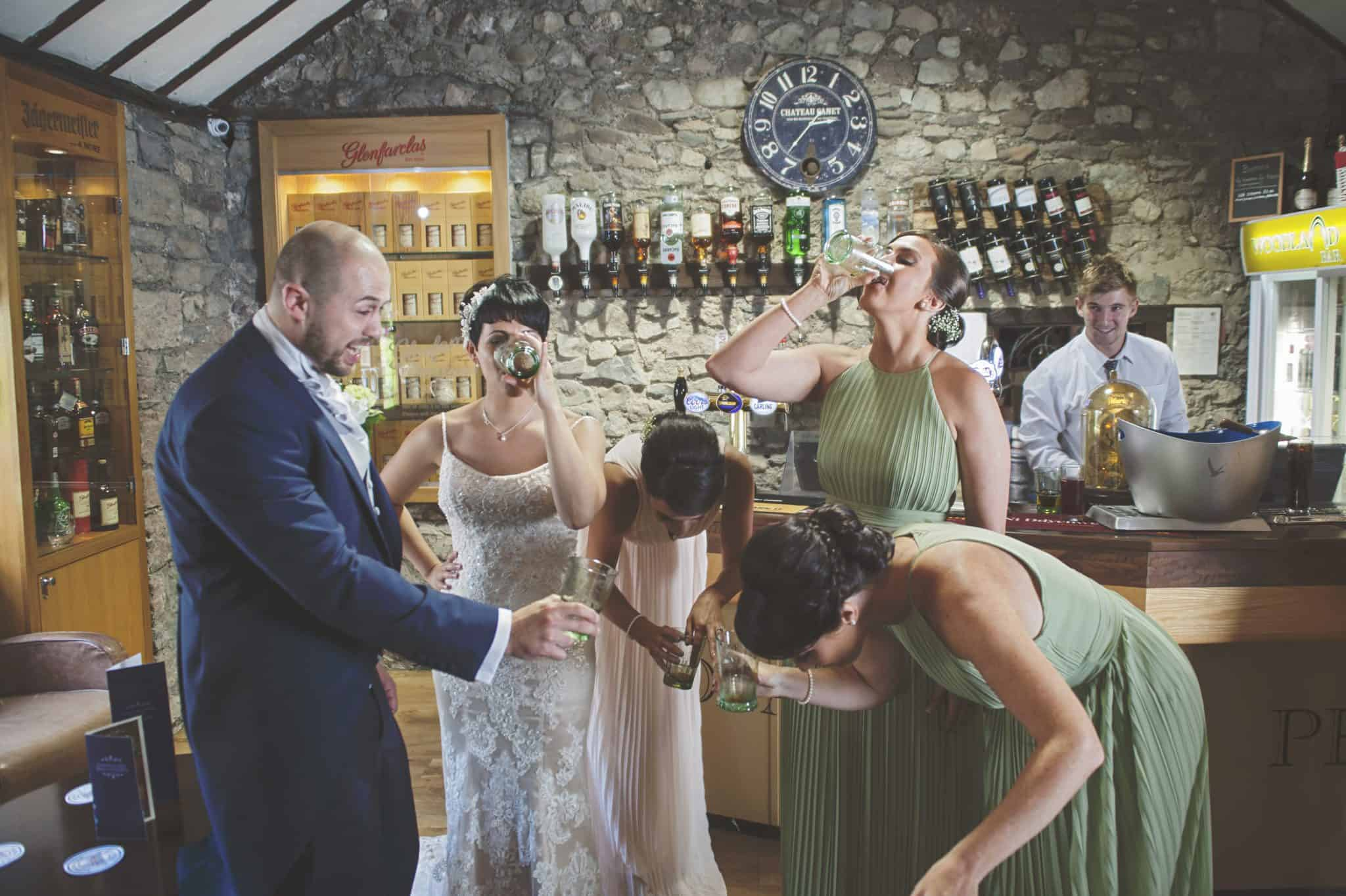 Groom, bride and bridesmaids doing shots and gagging