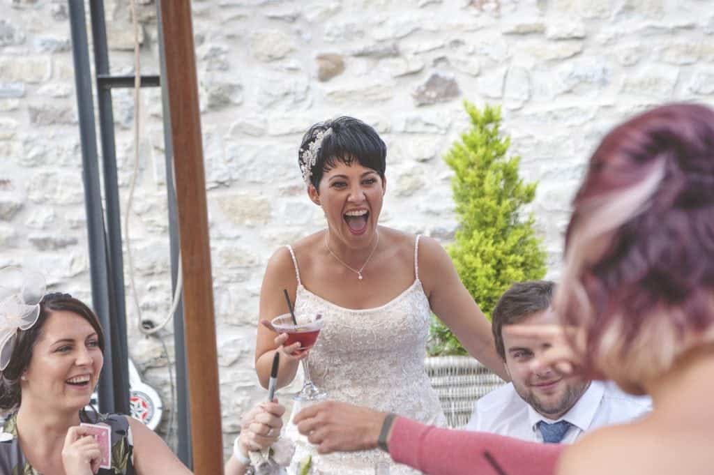 Bride laughing holding a cocktail