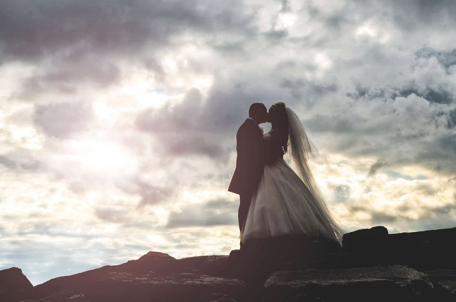 Bride & groom stood on top of cliff silhouetted against the cloudy sky