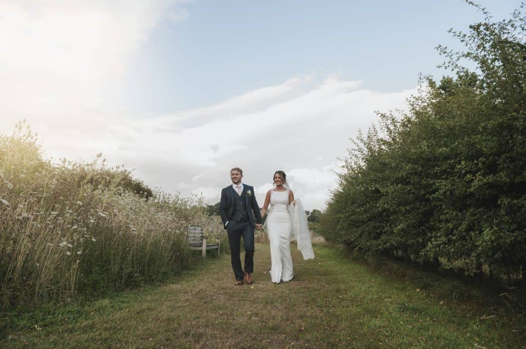 Bride & Groom walking in field - wedding photographers cardiff