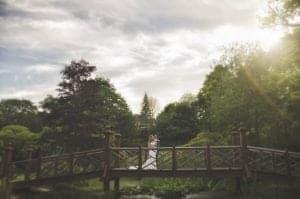 Bride and groom stood on wooden bridge