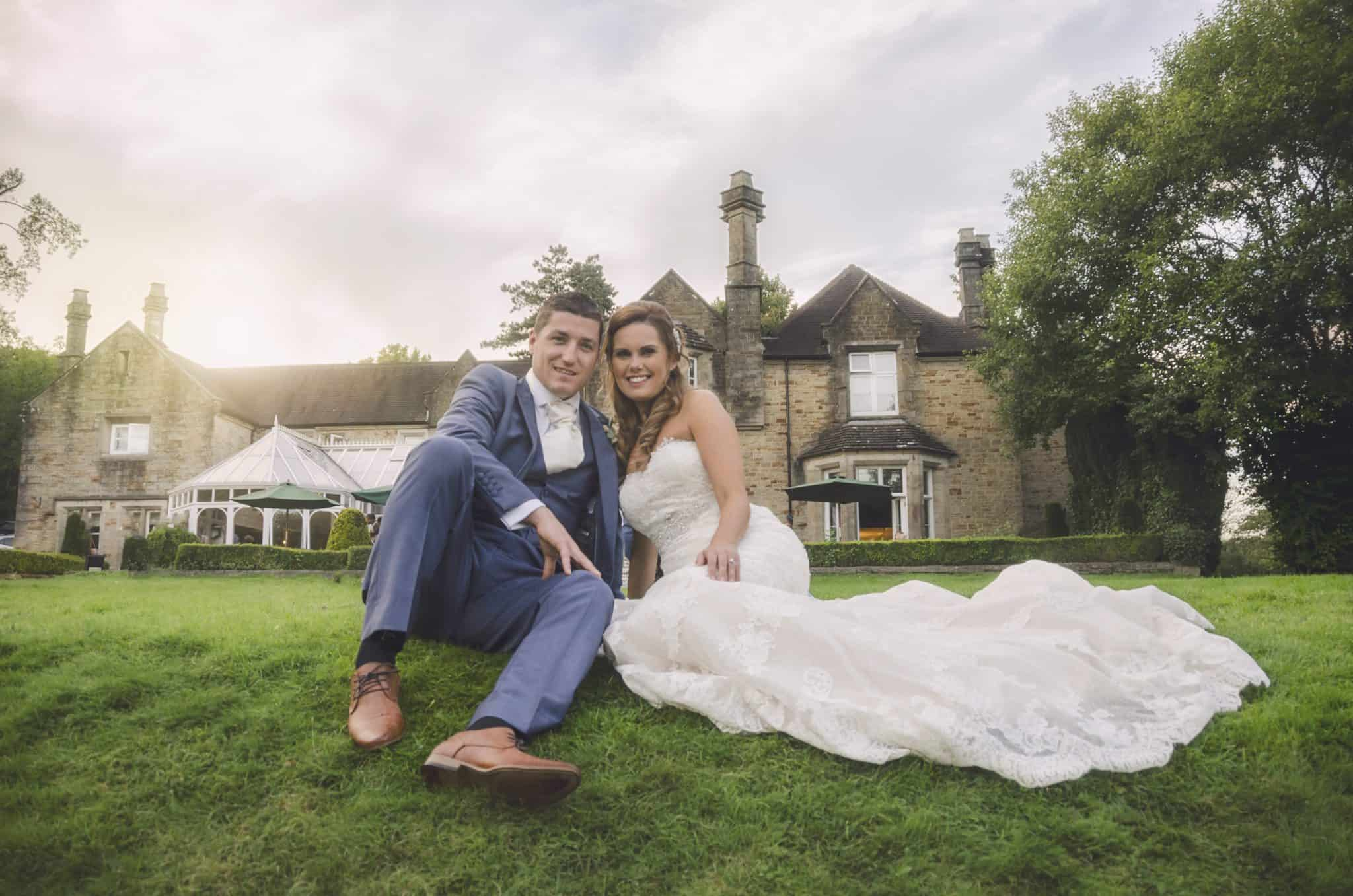 Bride and groom sat on grass bank in front of Bryngarw country house