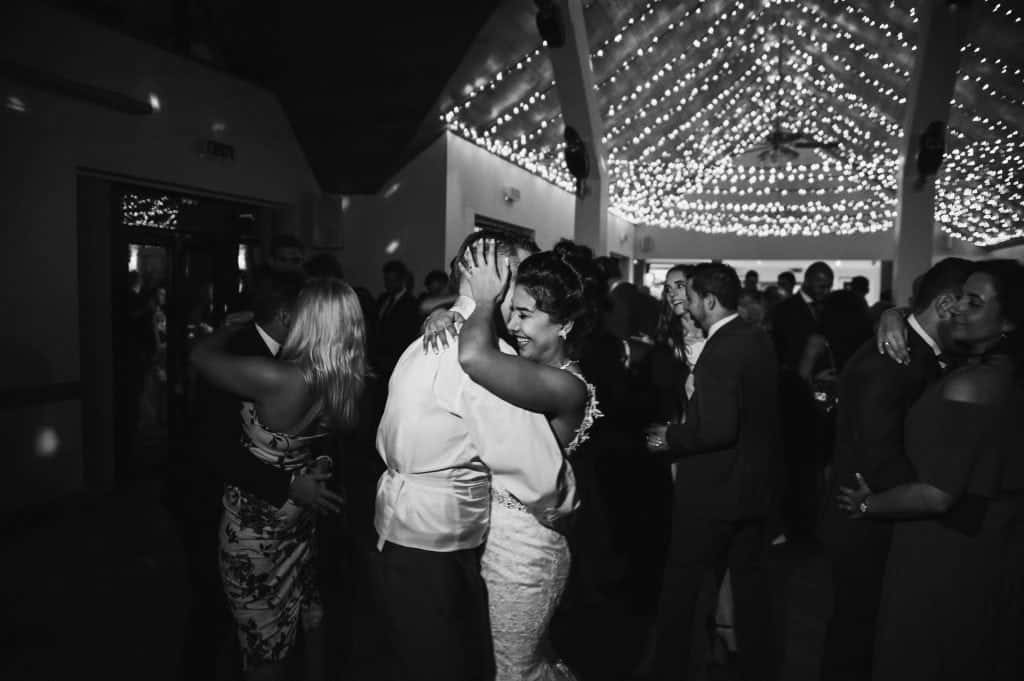 Bride hugs groom whilst dancing in fairy light lit room