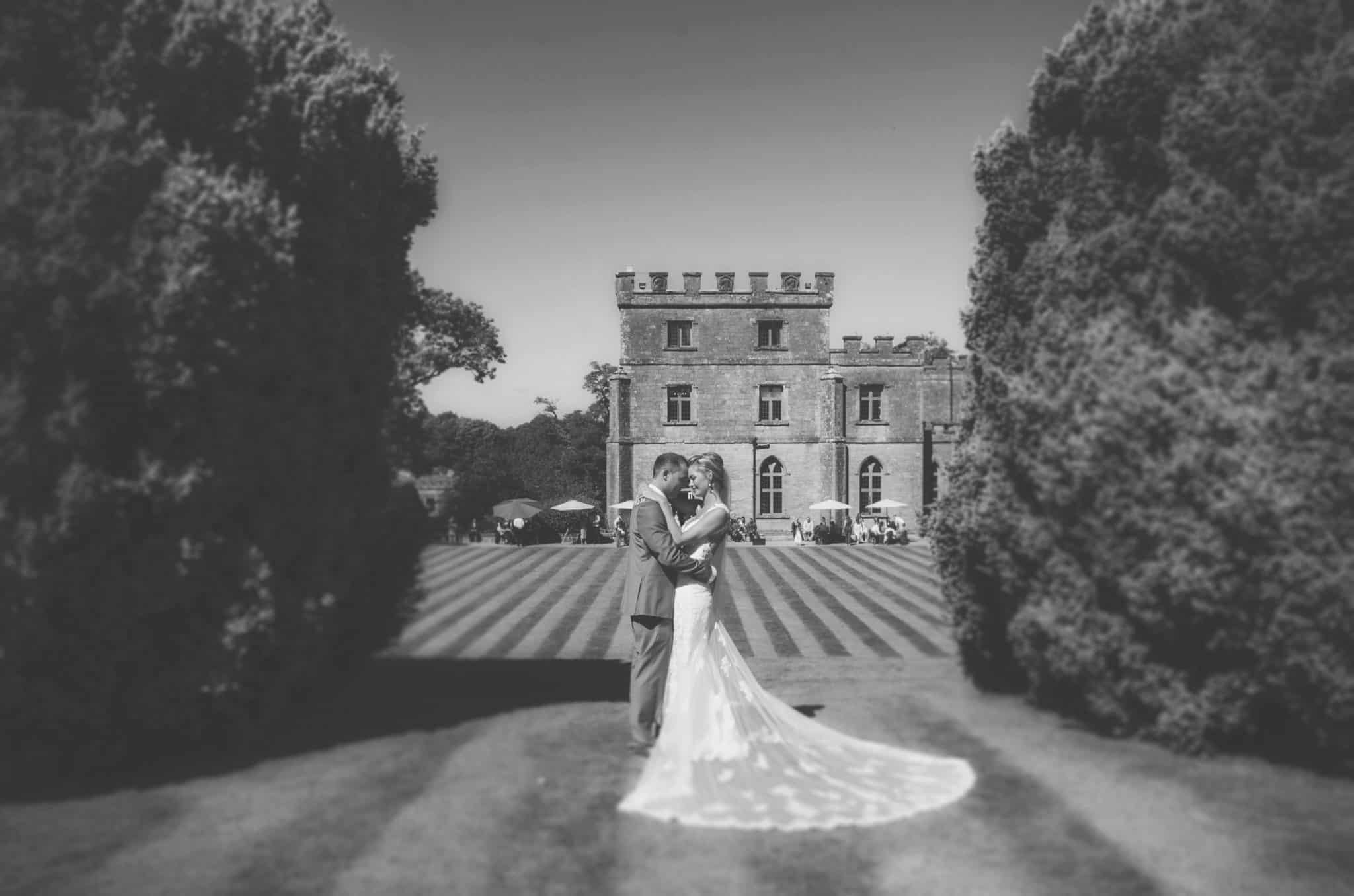 Bride & groom stood in between to hedges with Clearwell Castle in the background.