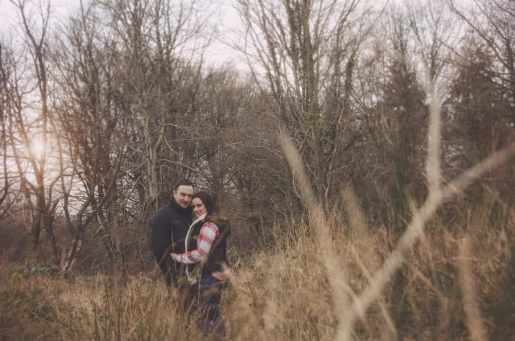 A young couple stood in long grass with the woman hugging the man smiling