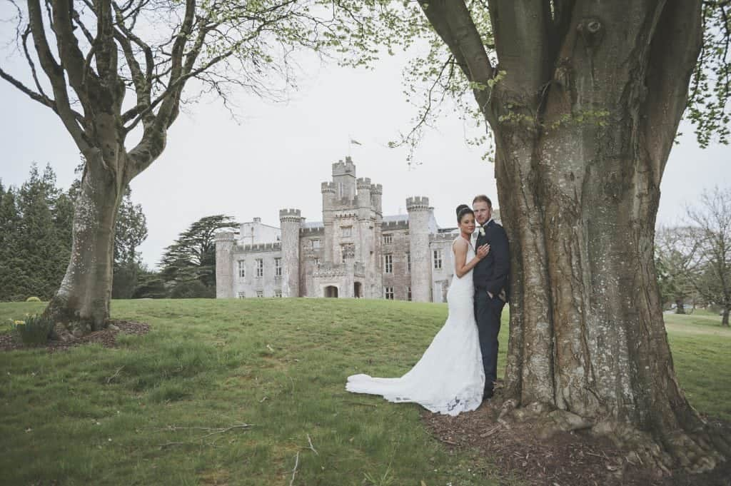 Bride & groom stood by tree in front of Hensol Castle