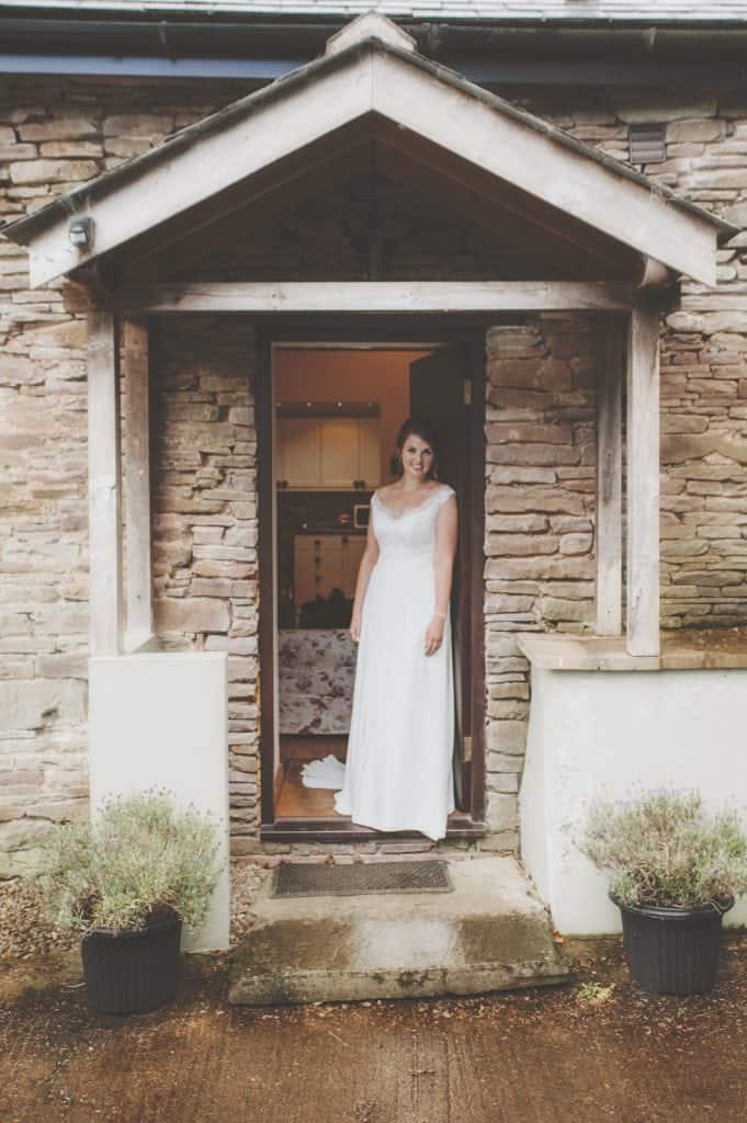 Bride stood in doorway of stone building