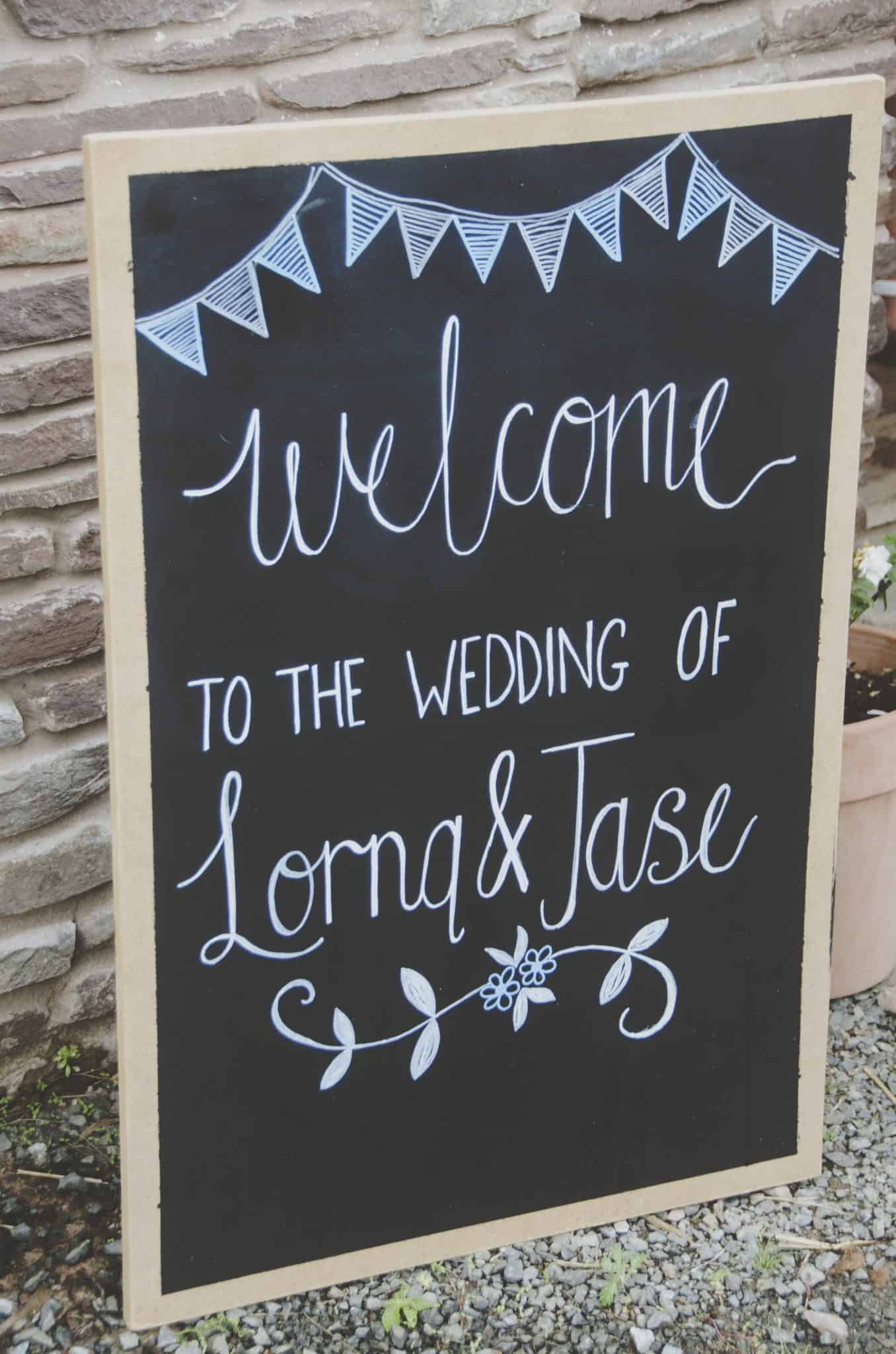 Welcome chalk board sign with bunting and flower motif