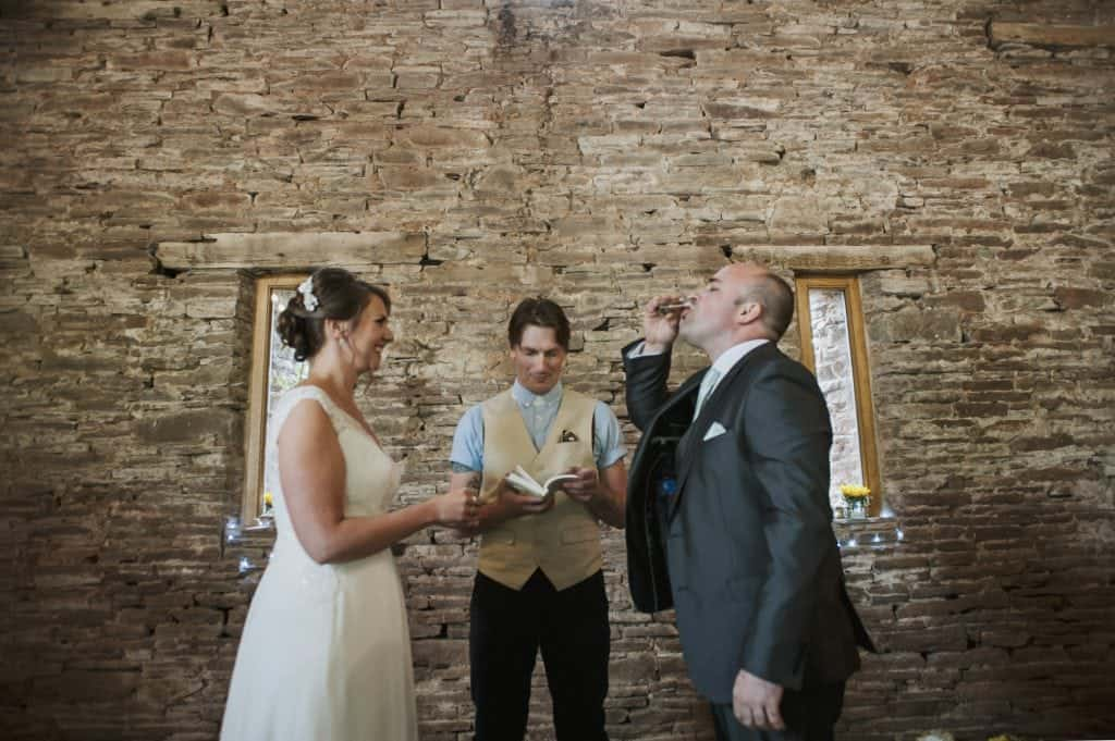Groom taking a shot as bride looks on