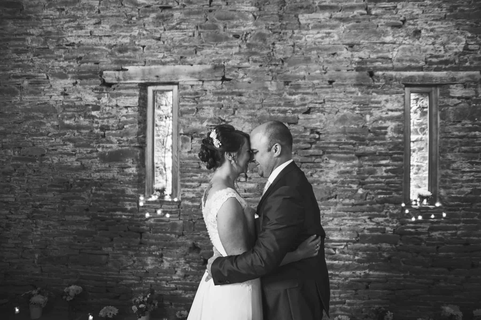 Bride & Groom embrace at a rustic barn wedding ceremony