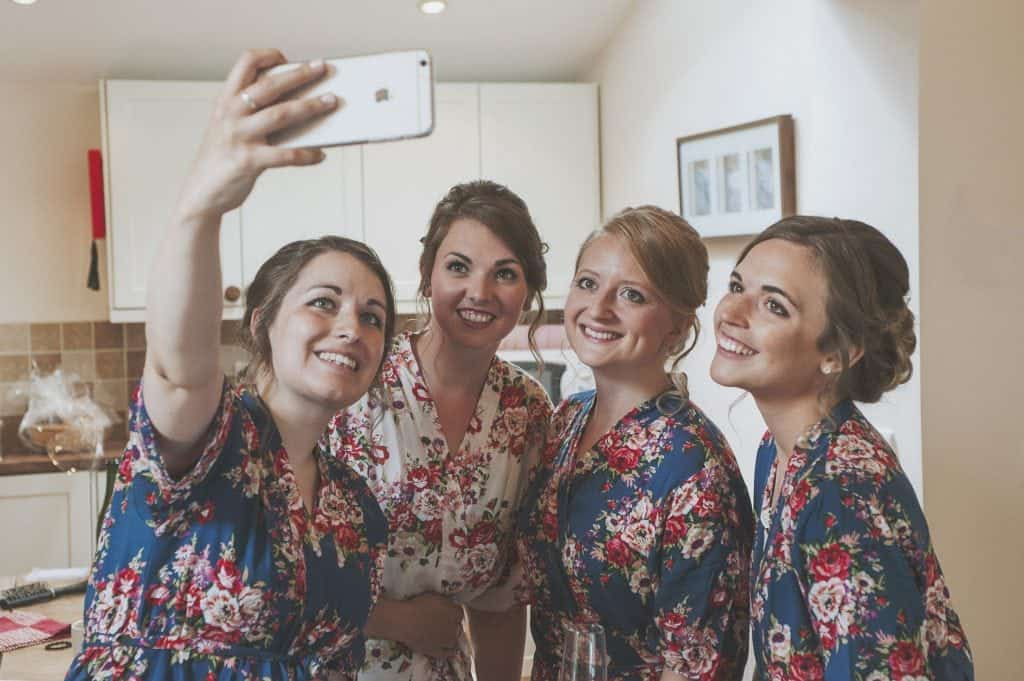 Bride and Bridesmaids taking a selfie in a kitchen