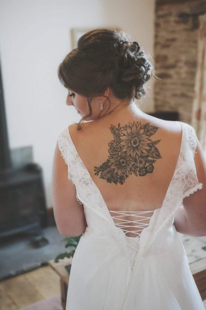 Bride stood in room with her wedding dress unbuttoned over her shoulders showing her flower tattoo on his upper back