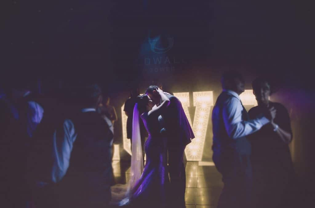 Bride & Groom Kiss on dance floor with large letters spelling the world love lit up behind them
