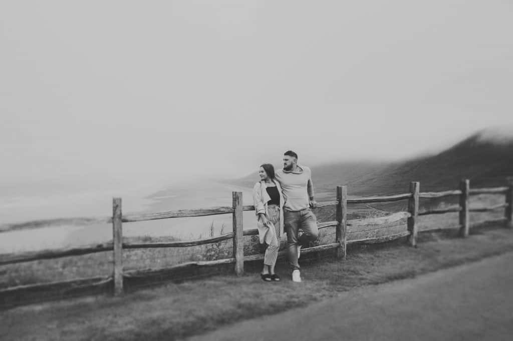 a couple stood against a wooden fence looking to the left with a Misty beach behind them