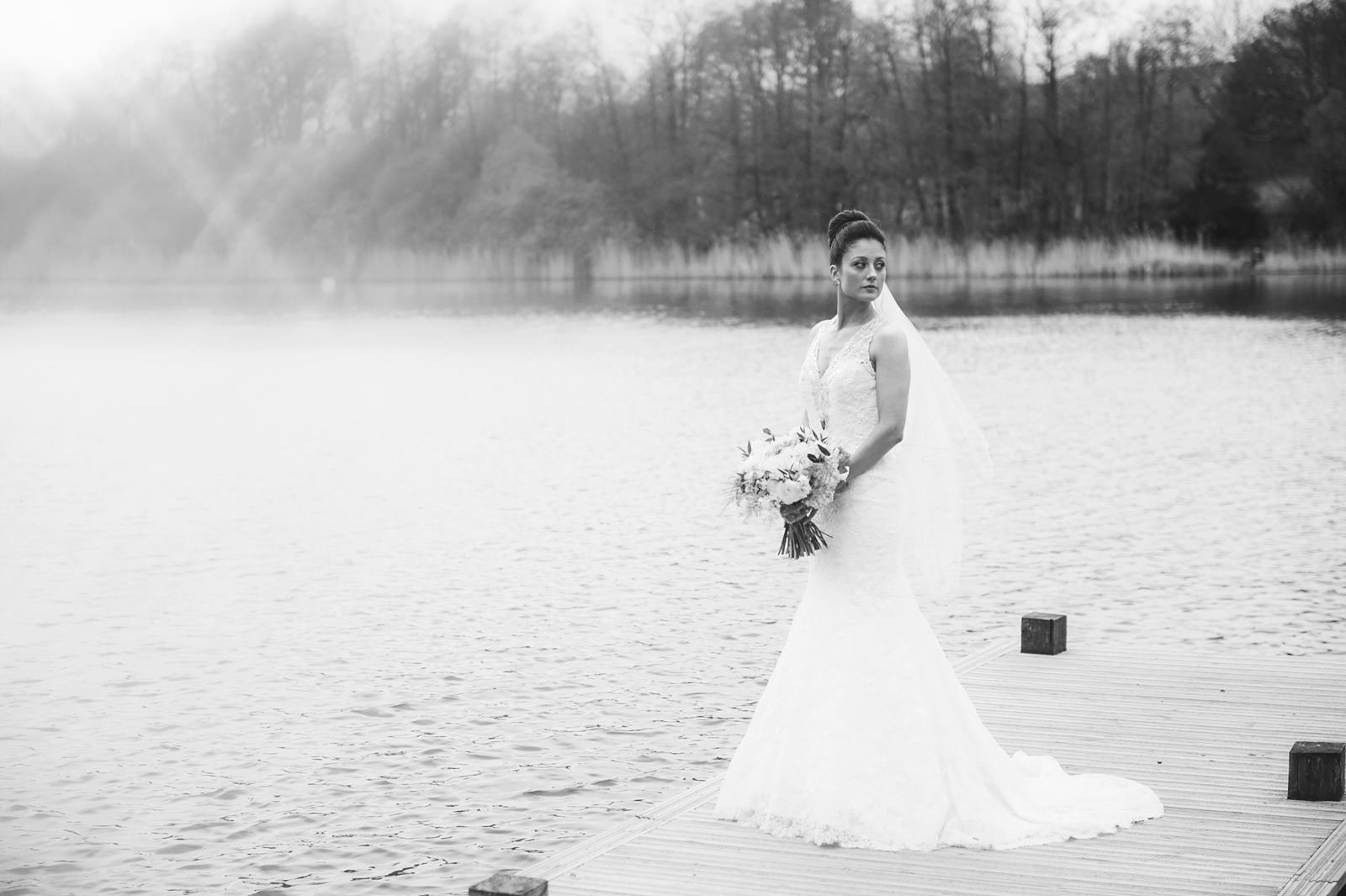 Bride stood on a jetty, holding wedding flowers looking to the left with a lake and tree line in background.
