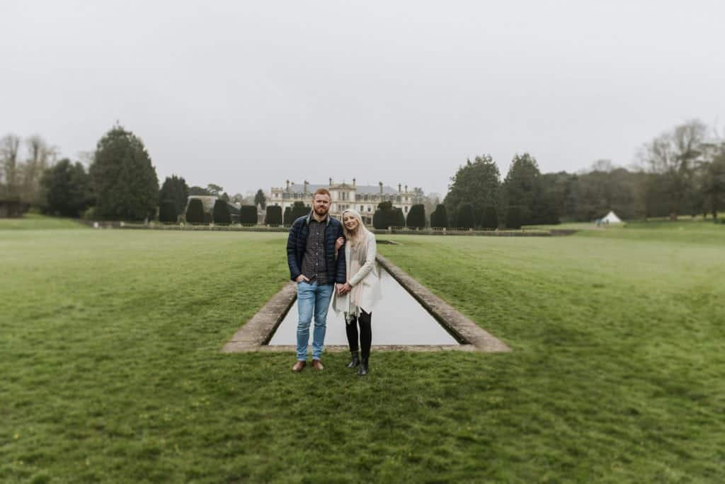 Couple stood in front of a small water way in front of a stately house for their Dyffryn Gardens Pre Wedding Photo Shoot