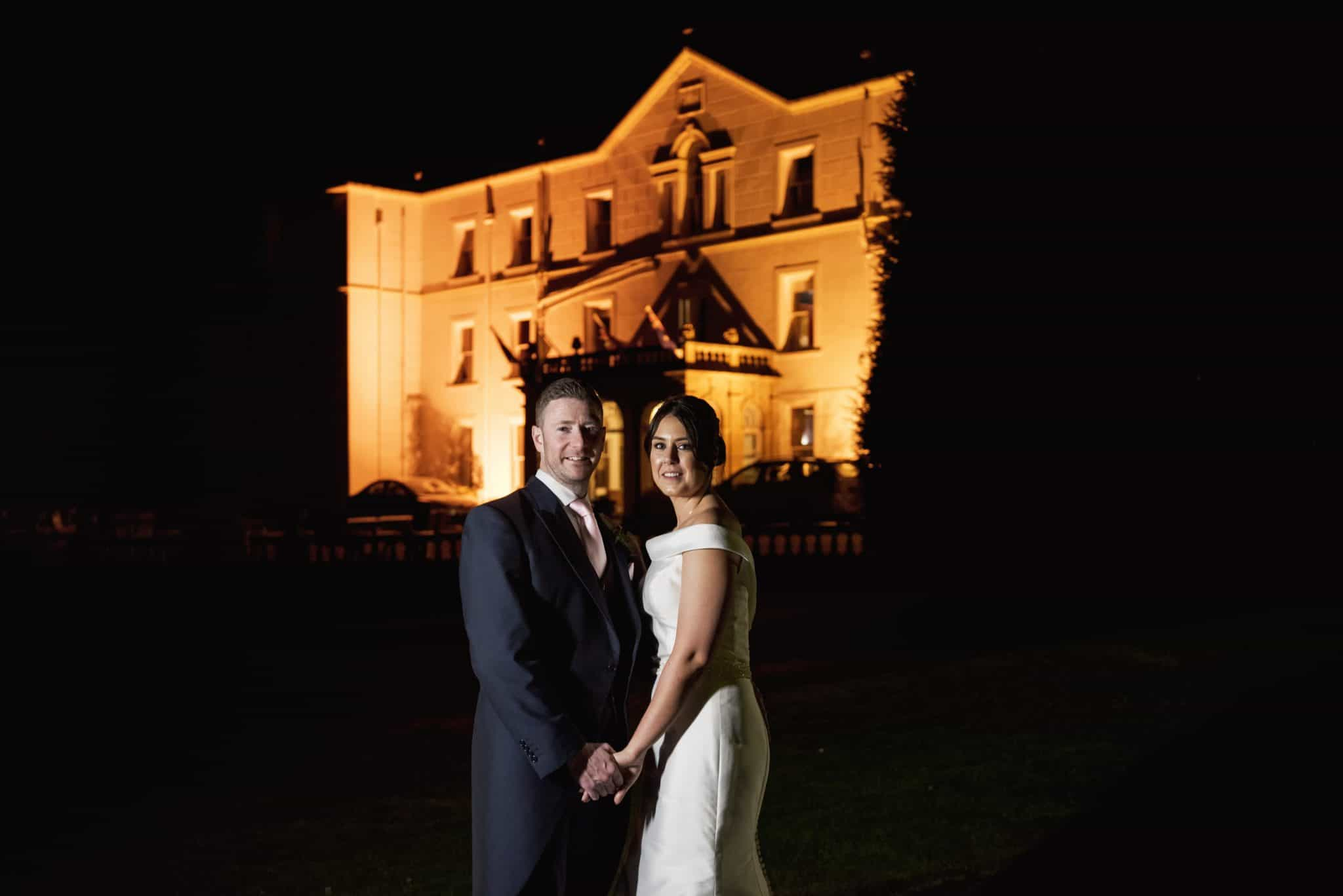 Bride and Groom stood at night time in front of a lit up Court Colman Manor, Bridgend