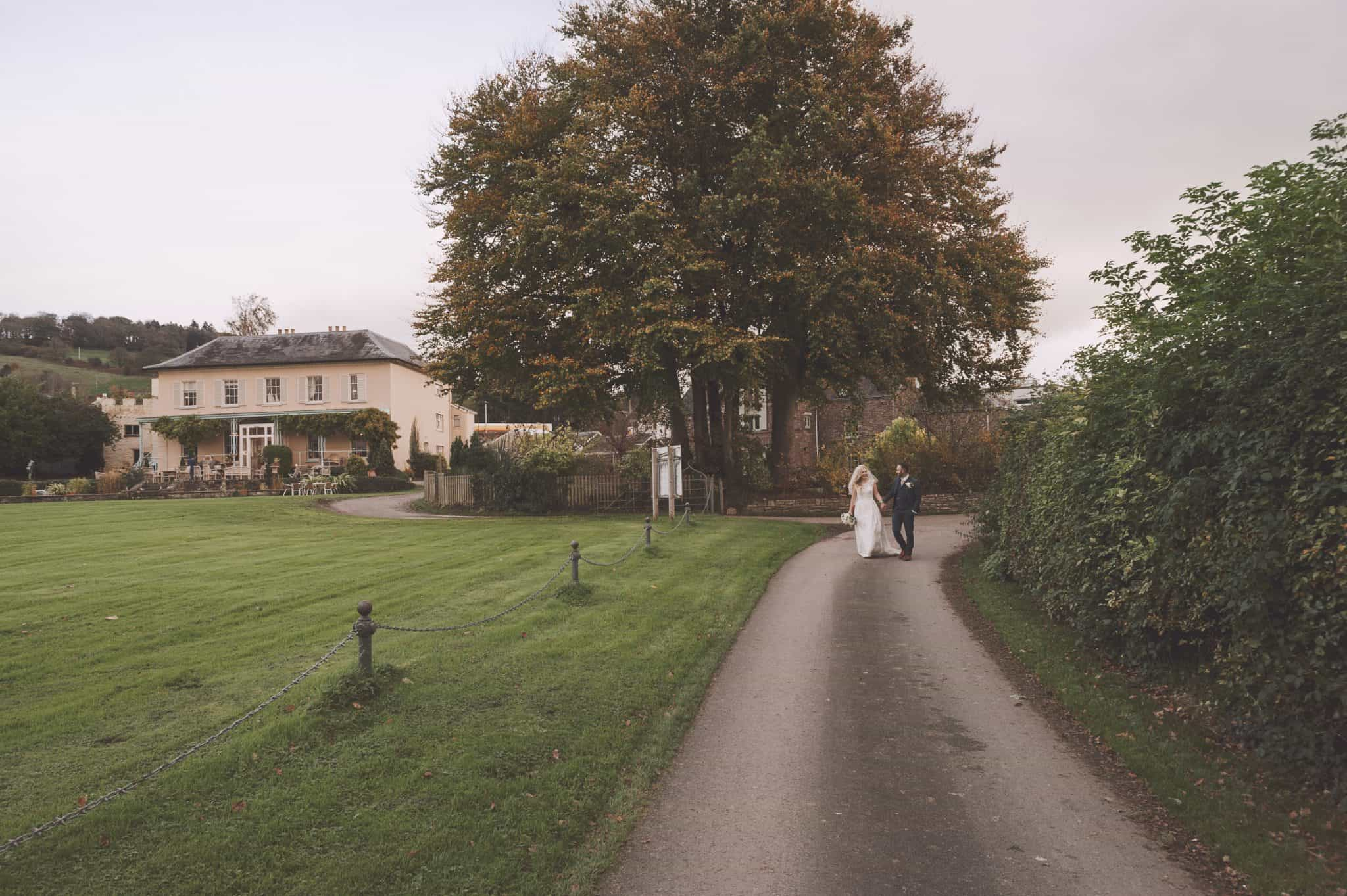 porthmawr country house wedding ~ Bride & Groom Walking down a path in front of a country house