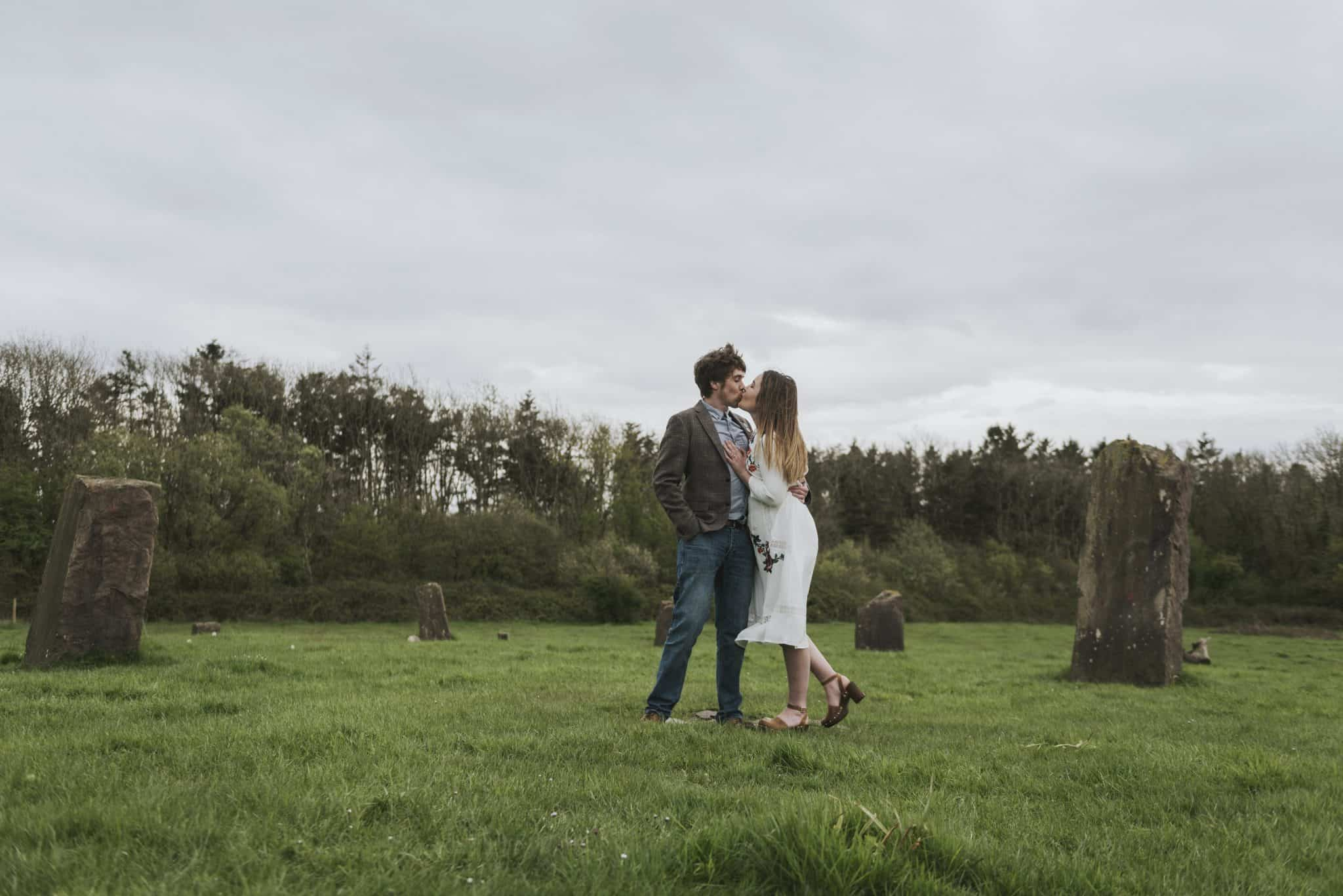 coed weddings pre wedding shoot ~ Couple kissing in a field surrounded by standing stones