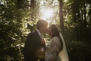 Bride & groom kissing in woodland with Sun setting behind them