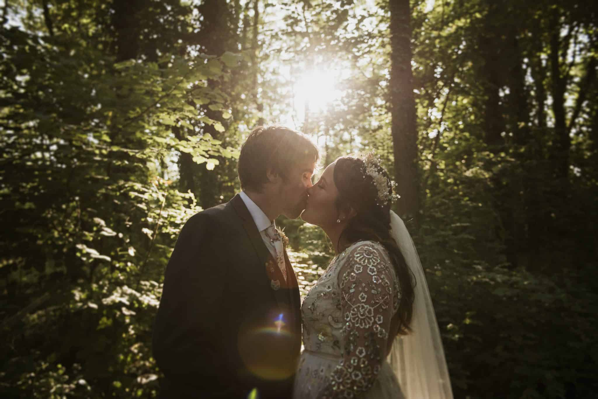 coed weddings ~ Bride & groom kissing in woodland with Sun setting behind them