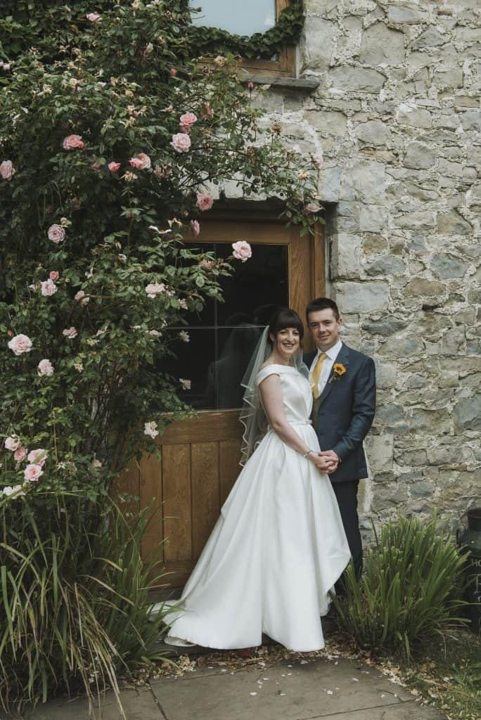 Bride & Groom stood next to Rose bush