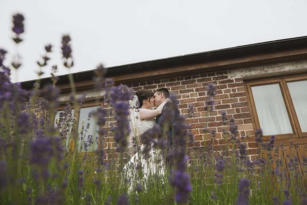 Bride & Groom kiss in front of lavender