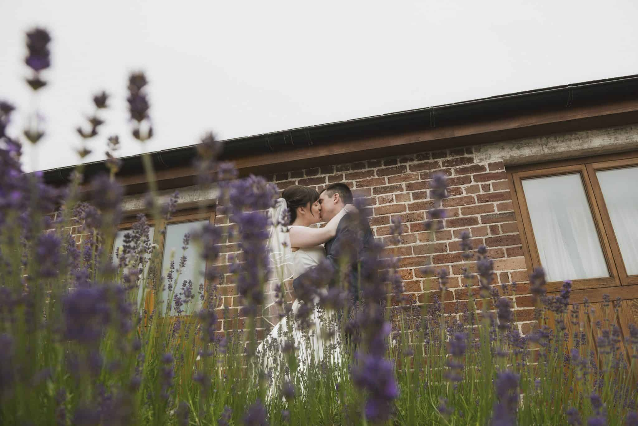Bride & Groom kiss in front of lavender