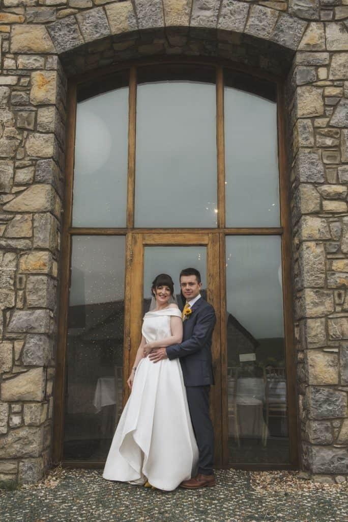 Bride & Groom stood in front on large windows