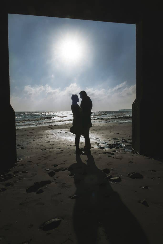 silhouette of couple stood on beach