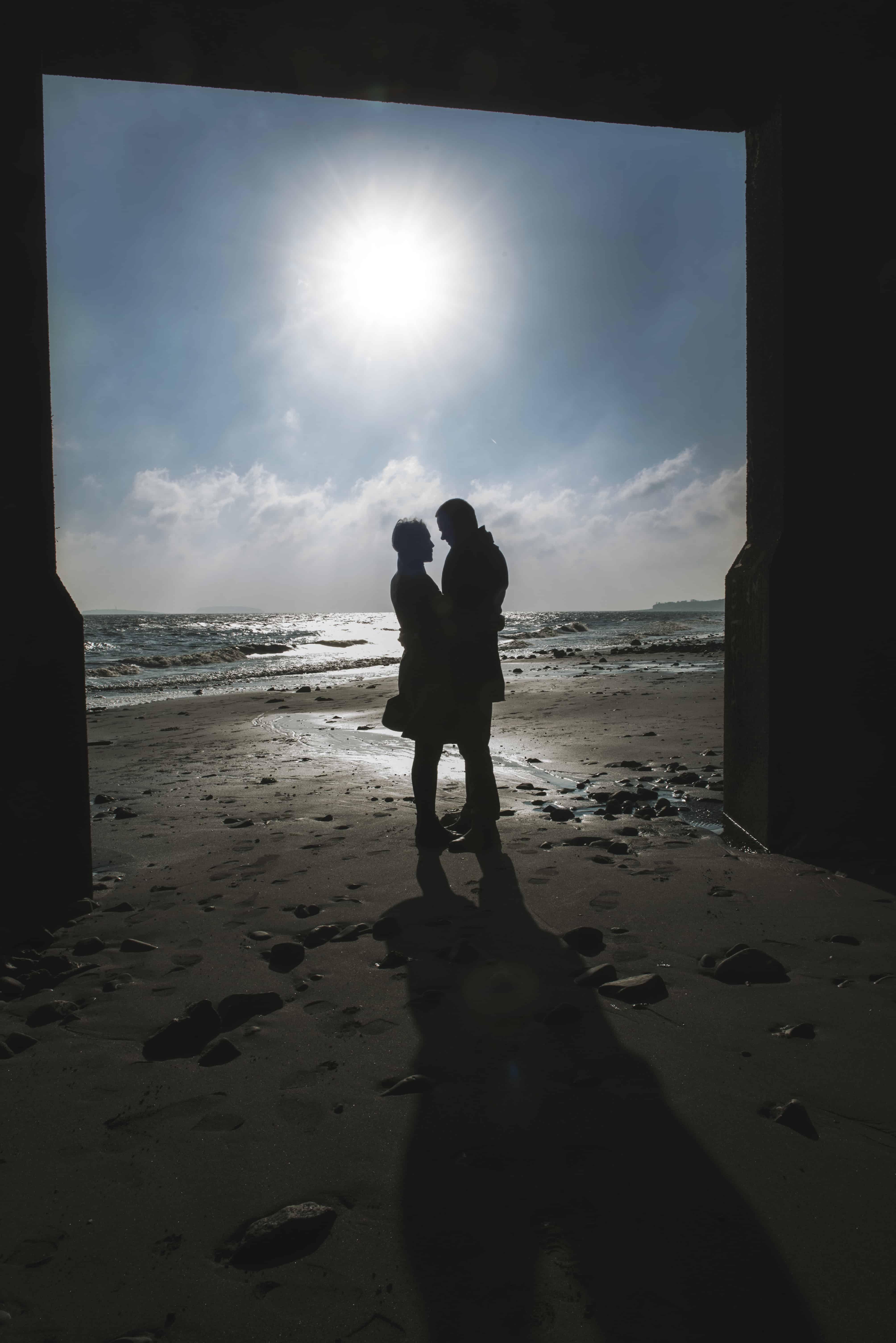 silhouette of couple stood on beach