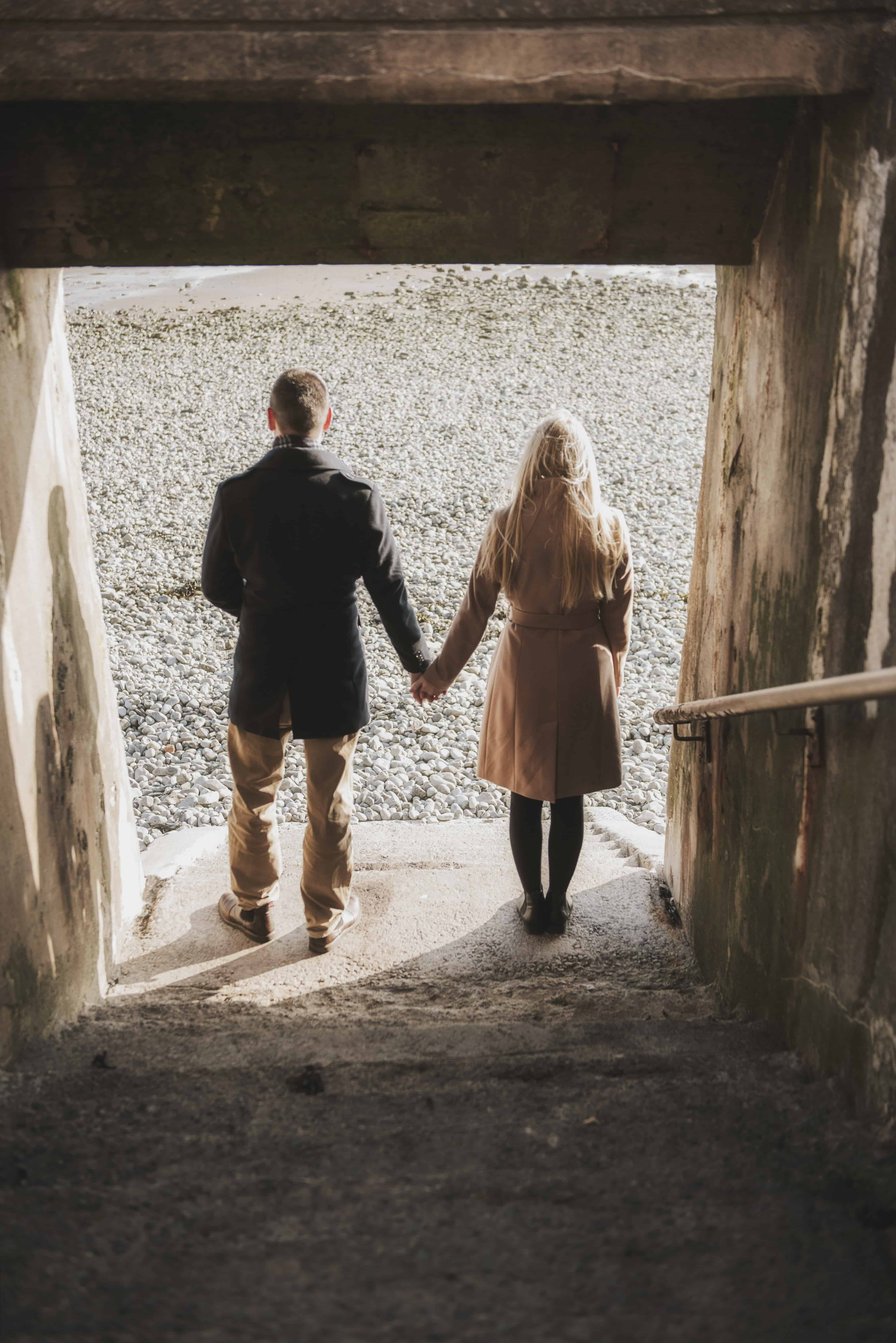 Couple stood at bottom of stair on beach