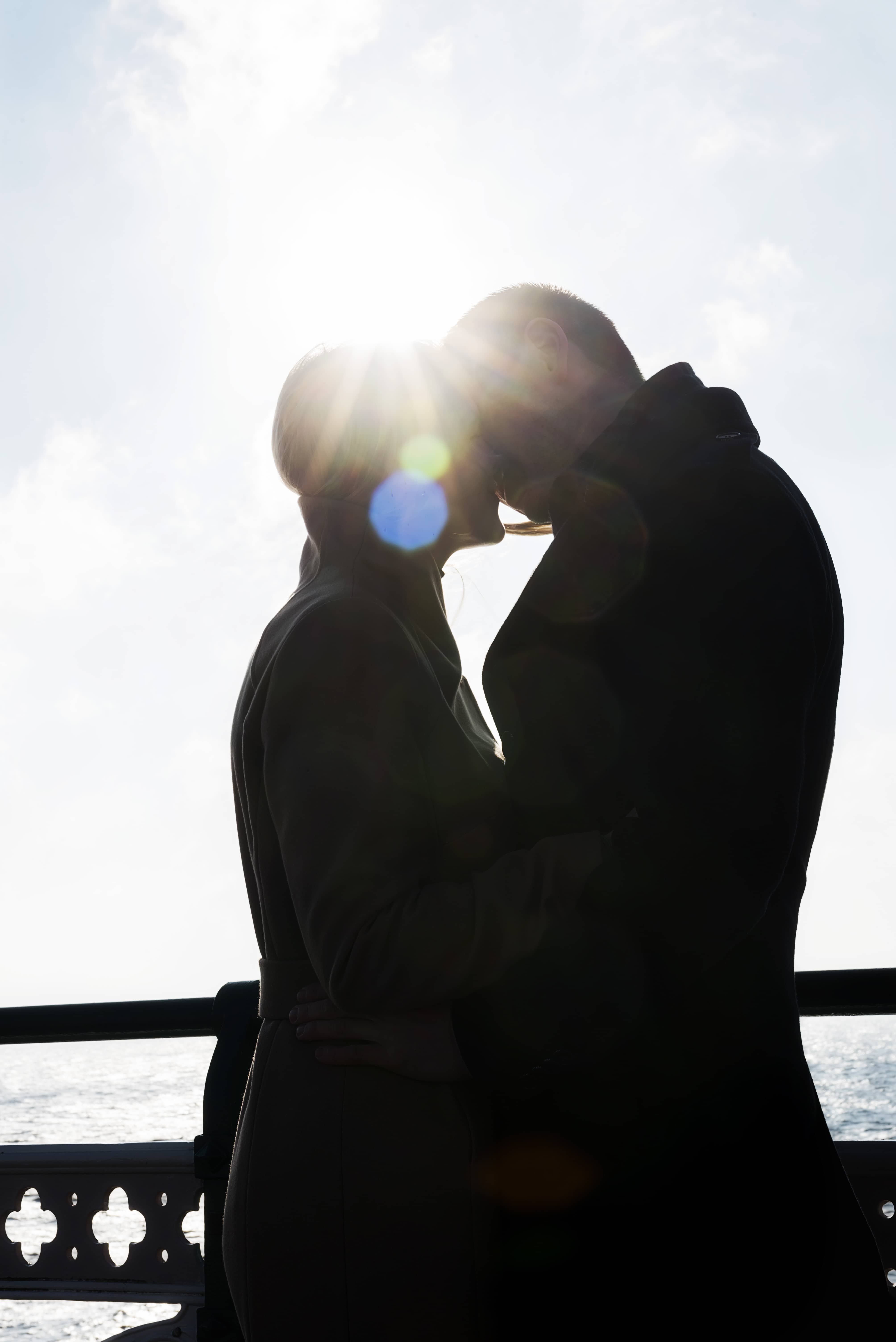 silhouette of couple on pier kissing