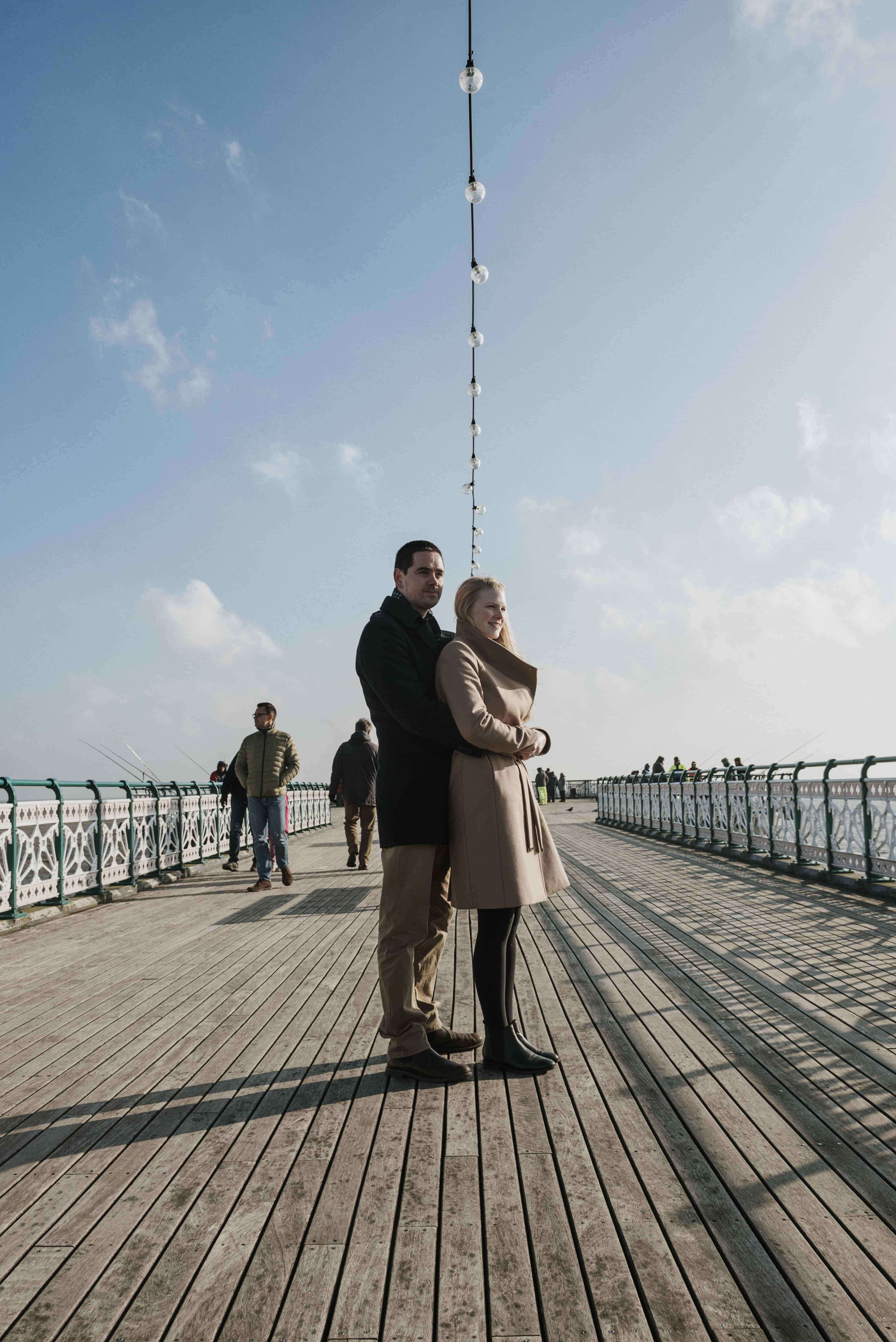 Couple stood on pier looking at the sea