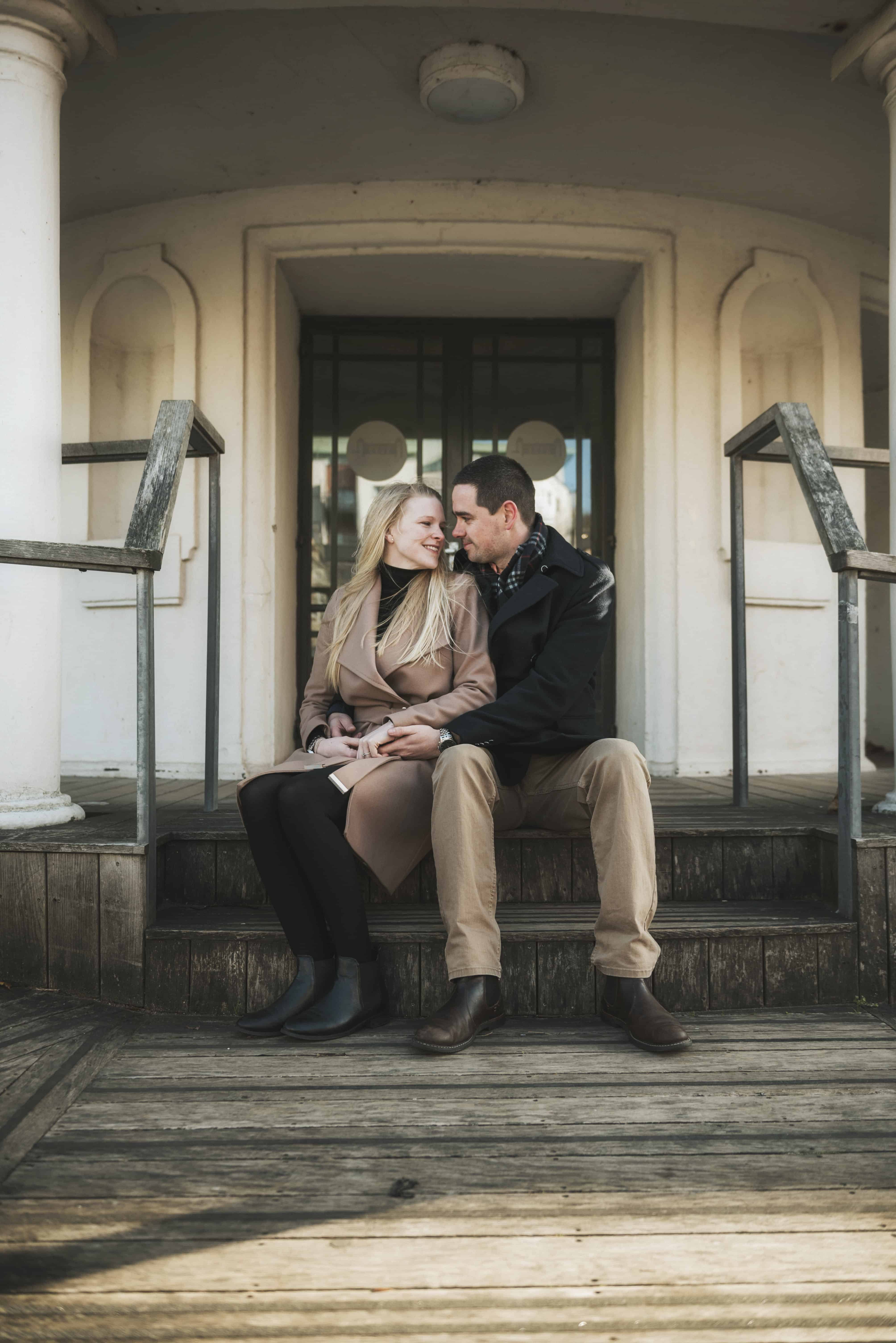 Couple sat on steps looking at each other