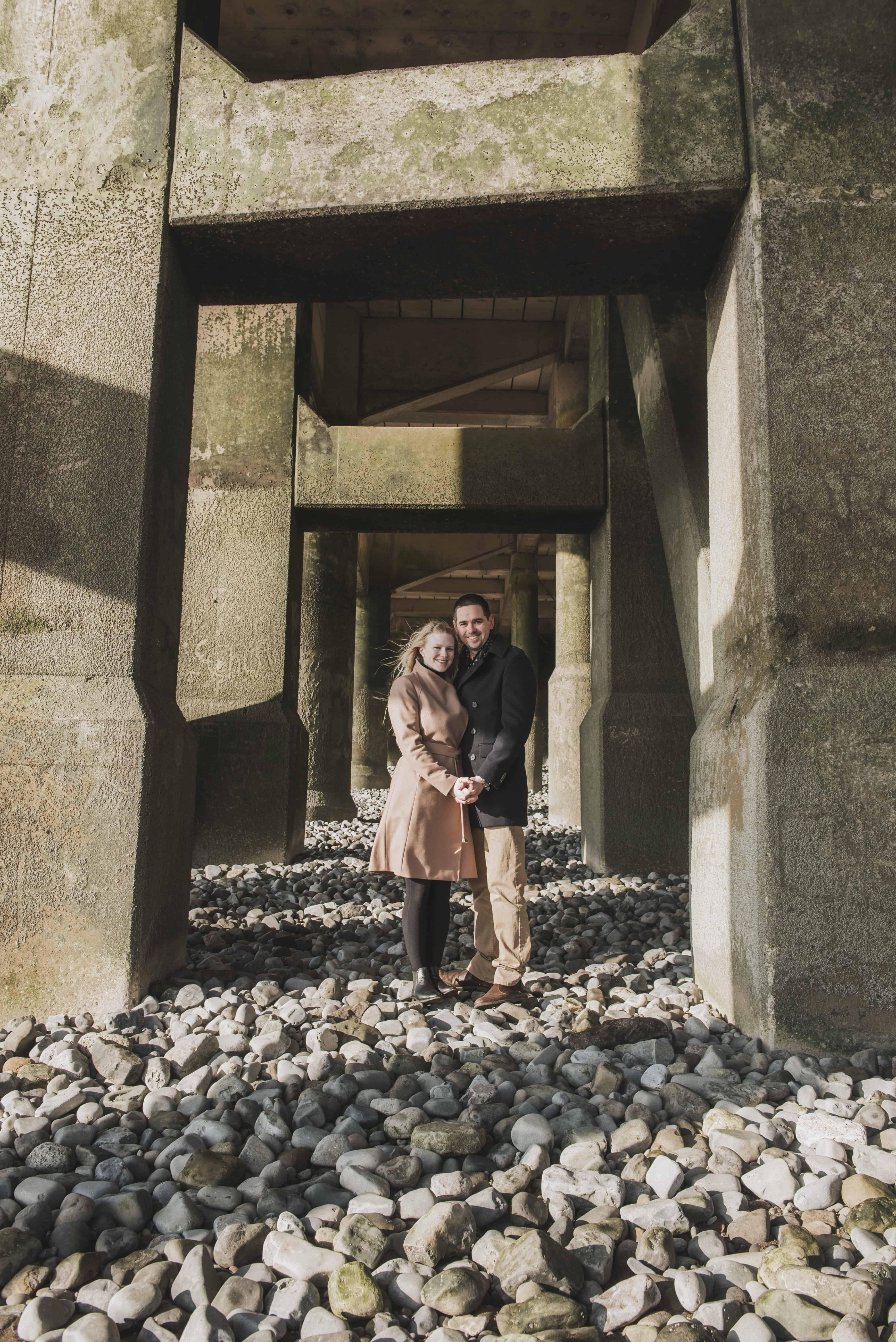 Couple stood under pier on pebbled beach