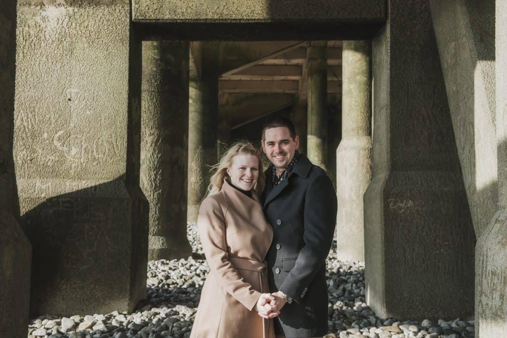 Couple stood under pier on beach