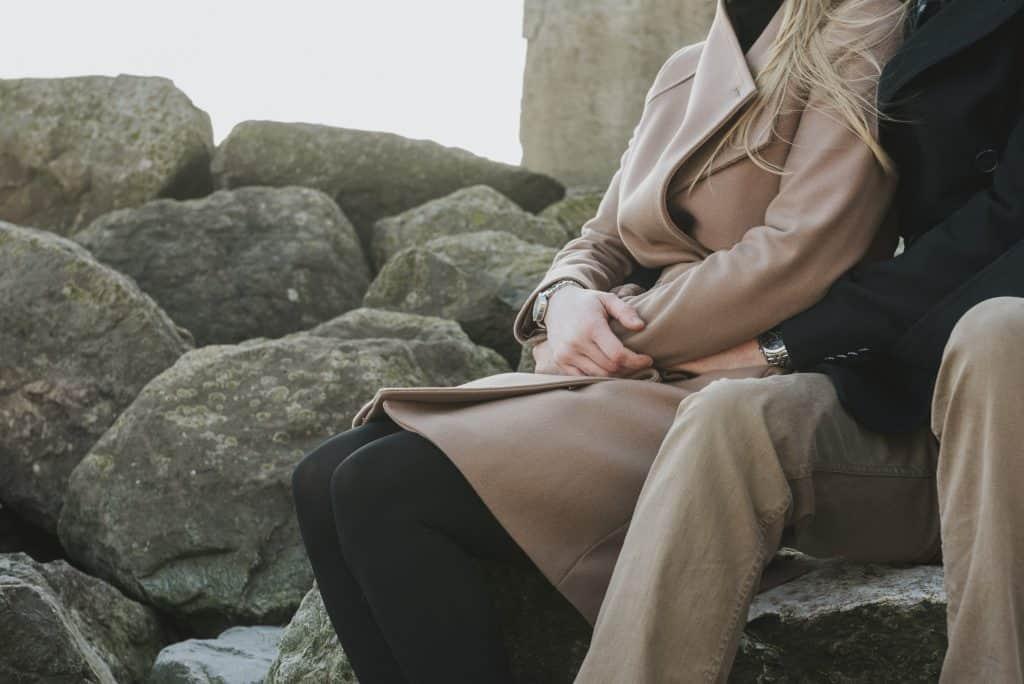 Couple sat on rocks at beach