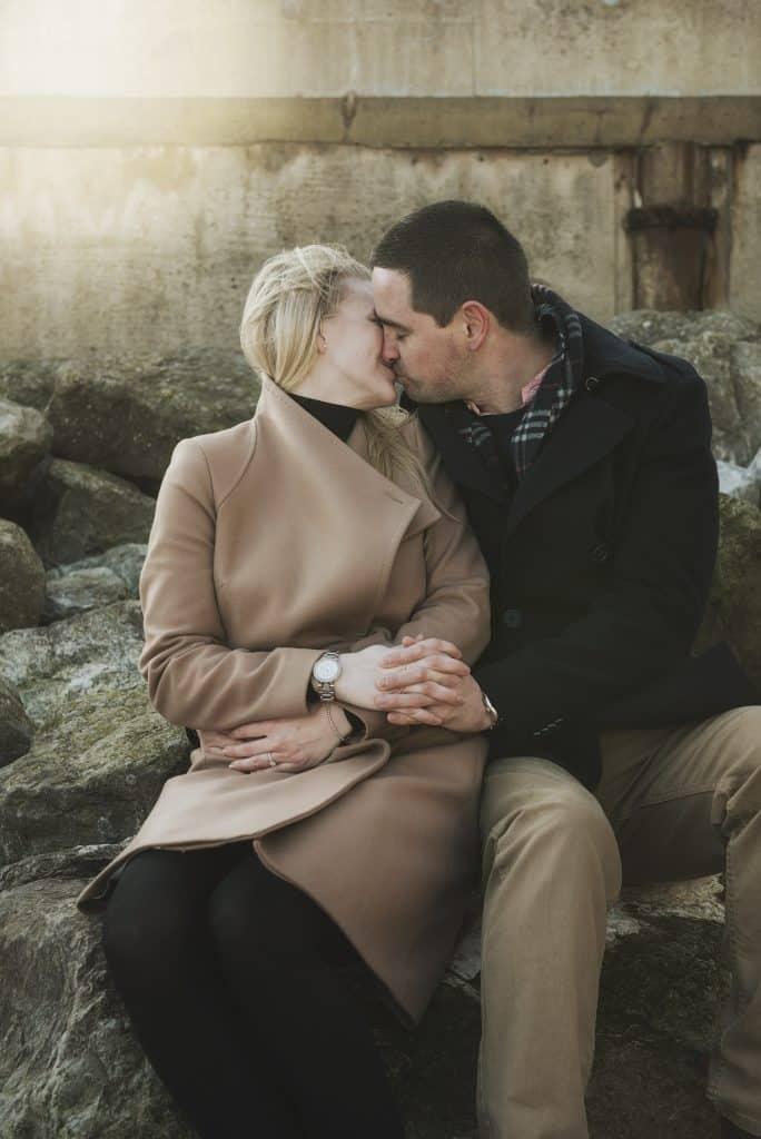 Couple sat on rocks kissing