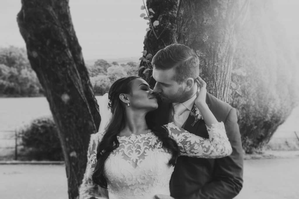 Bride & groom kiss in front of a tree