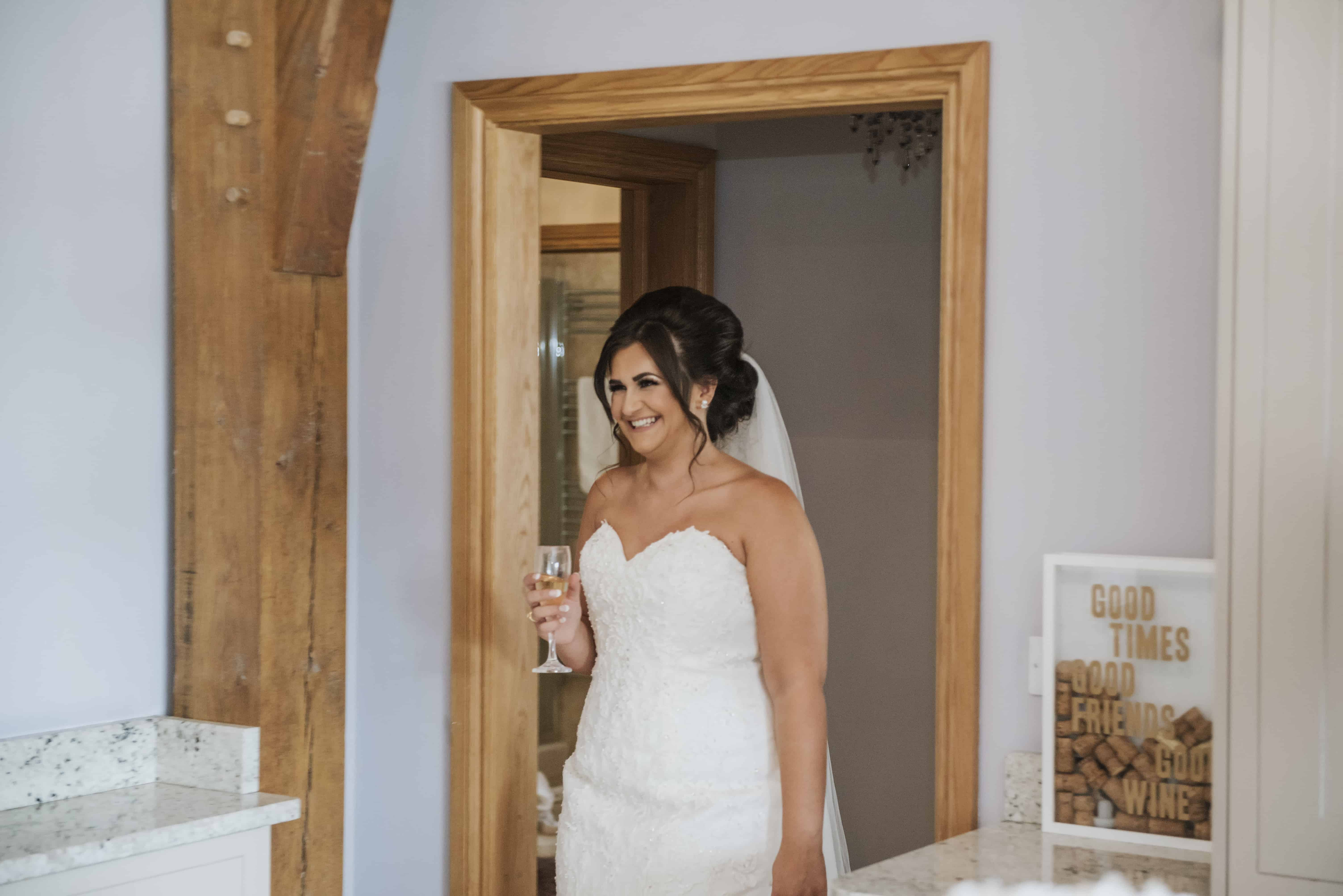 Bride stood smiling holding a glass of champagne Wedding Photographer