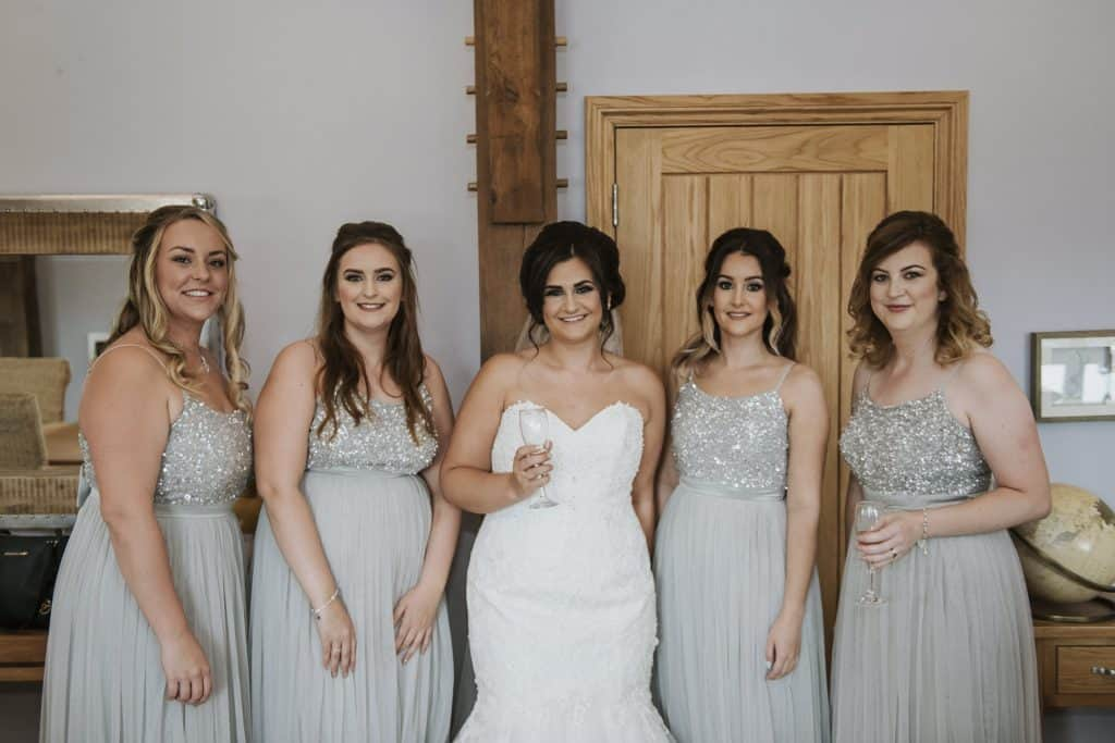 Bride 7 bridesmaids stood smiling Oldwalls Wedding Photographer