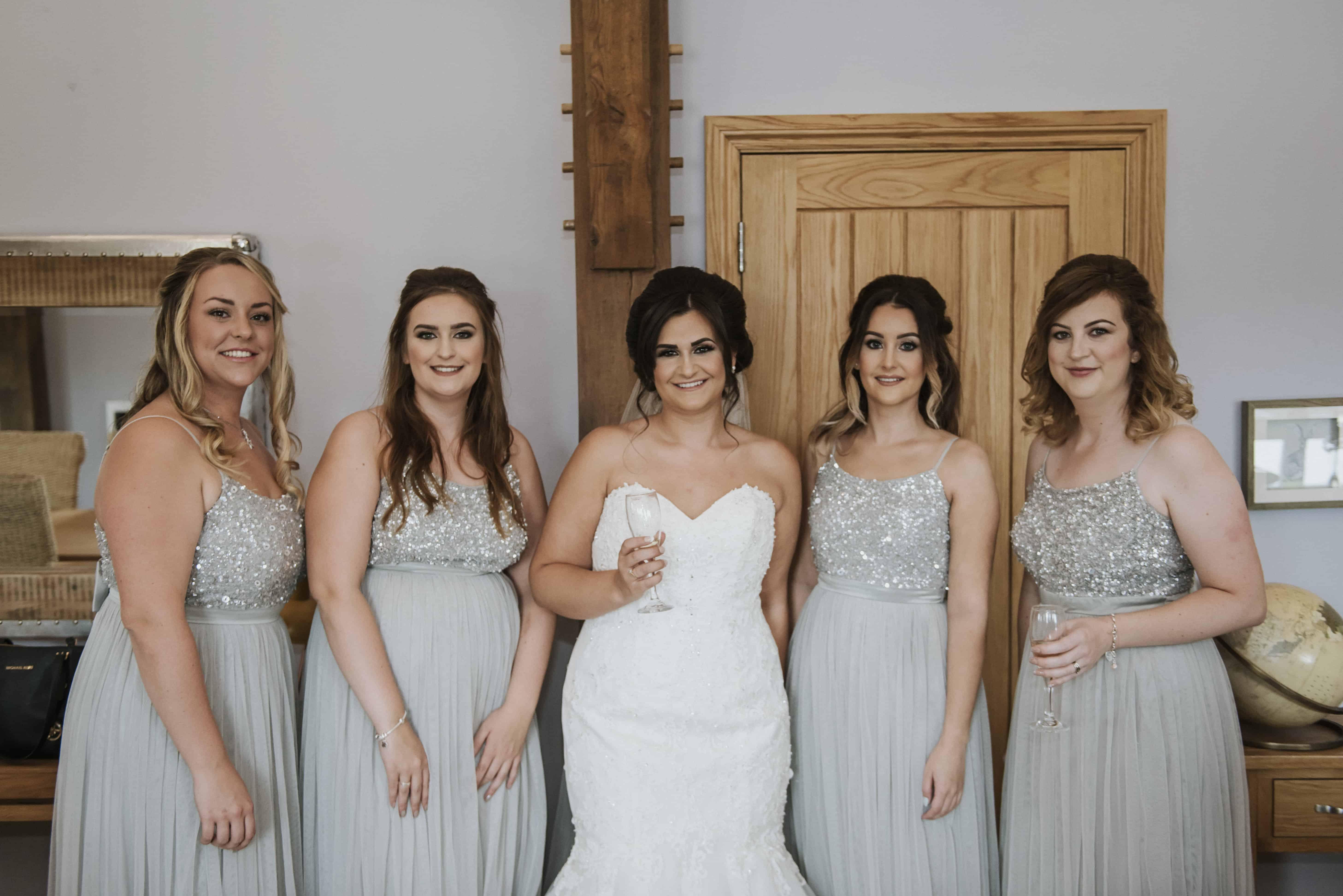 Bride 7 bridesmaids stood smiling Oldwalls Wedding Photographer