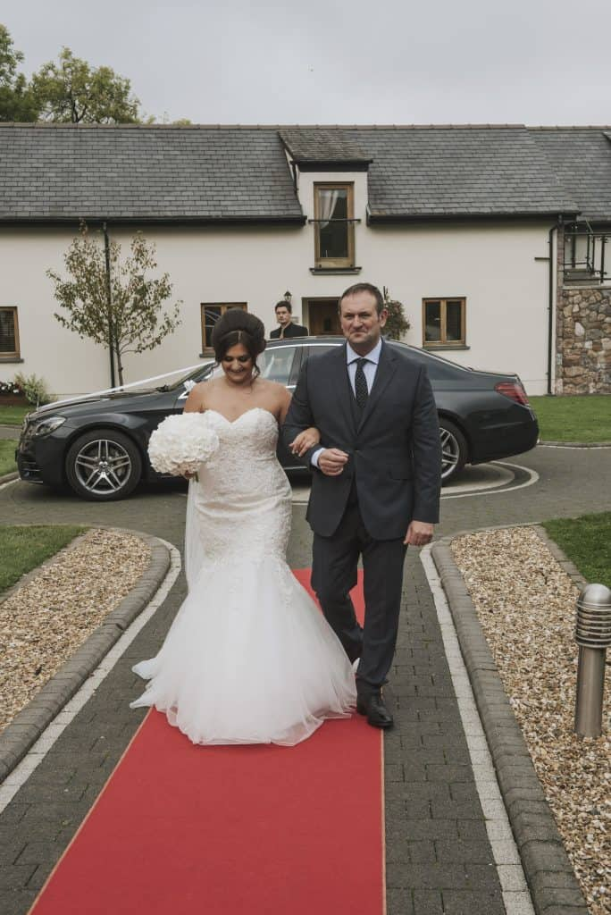 Bride & father walking on red carpet Oldwalls Wedding Photographer
