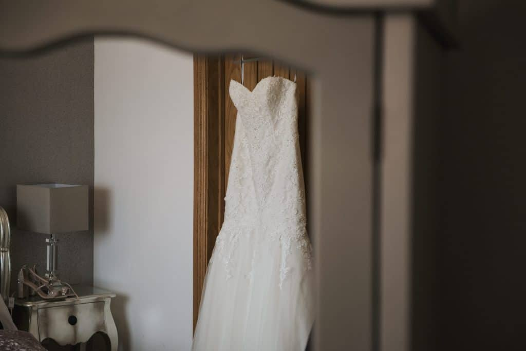 Wedding dress handing on bedroom door Oldwalls Wedding Photographer