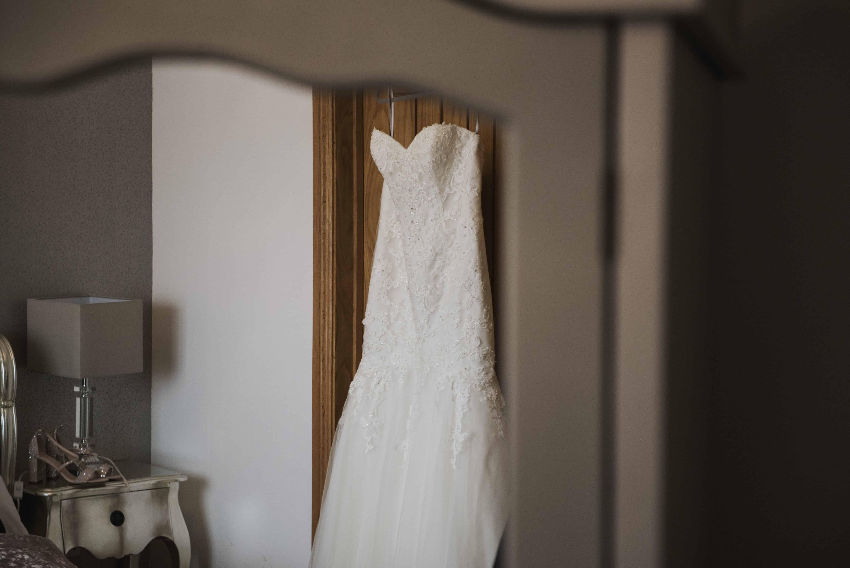 Wedding dress handing on bedroom door Oldwalls Wedding Photographer