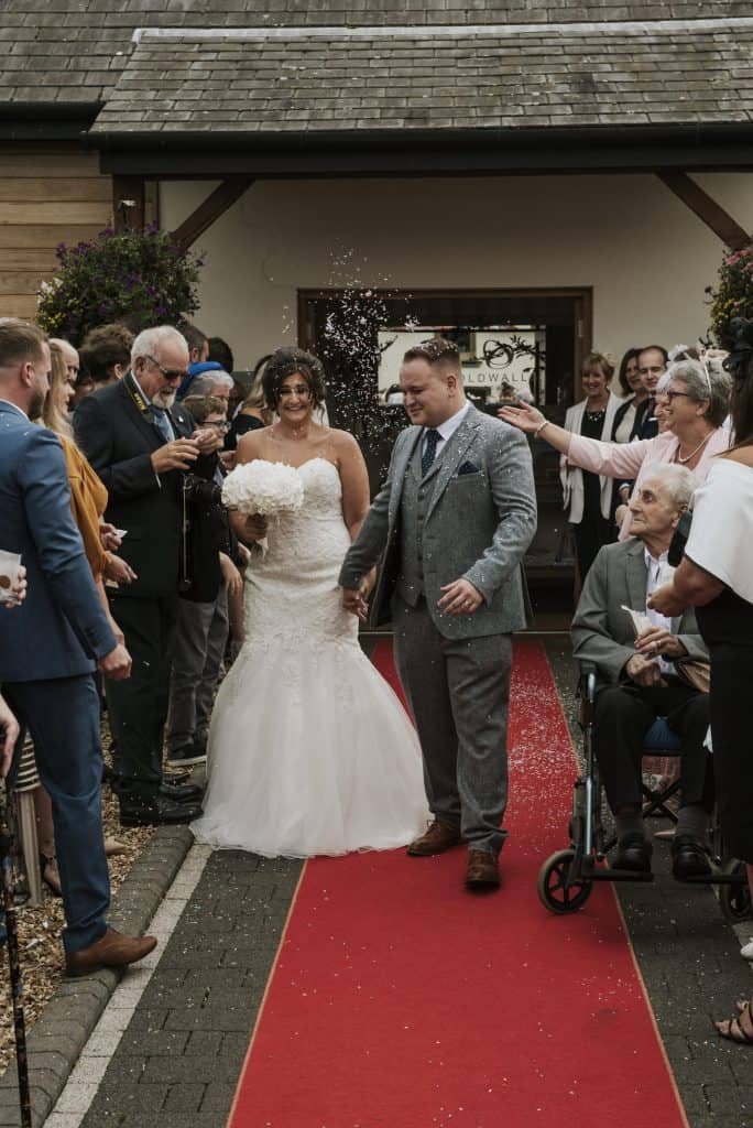 Bride and groom walk down red carpet whilst guest throw confetti  Oldwalls Wedding Photographer