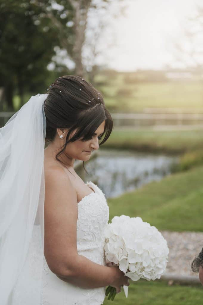 Bride holding her bouquet looking down Oldwalls Wedding Photographer