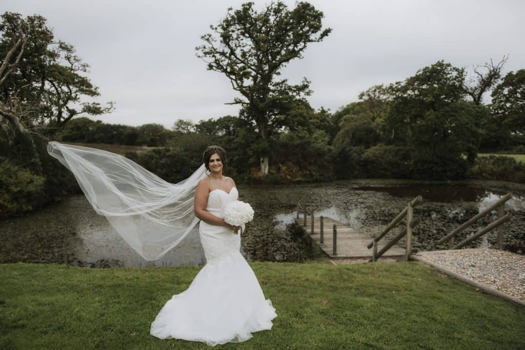 Bride stood on grass in front of lake Oldwalls Wedding Photographer